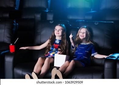 Surprised smiling little girls sitting at the cinema, watching a film and eating popcorn. movie theater.