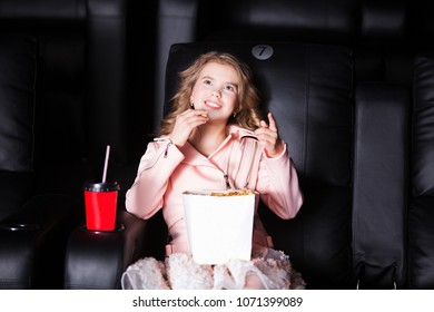 Surprised smiling teen girl sitting at the cinema, watching a film and eating popcorn. movie theater.