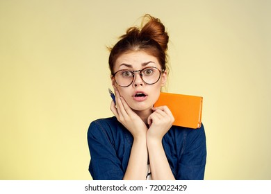 surprised student with glasses in hand notebook on yellow background portrait, study, university