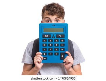 Surprised student holding big calculator. Portrait of funny cute teen boy, isolated on white background. Shocked child covered his face with calculator. Back to school.