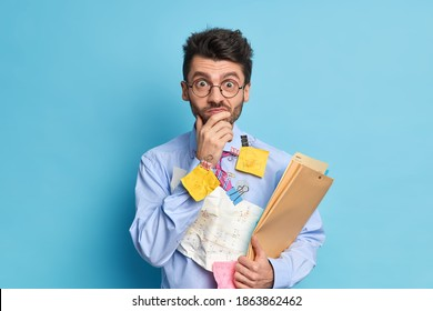 Surprised student prepares for exams at university studies economy wears blue shirt with stickers hanging on paperclips focused at camera. Male worker in formal clothes prepares business project