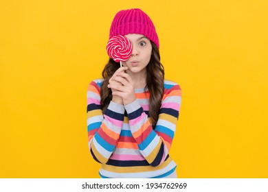 surprised teen girl hold lollipop. lollipop lady. hipster kid with colorful lollypop sugar candy on stick. caramel candy shop. sweet childhood life. concept of dental care. sweet tooth. yummy.