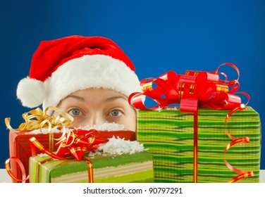 Surprised teen girl looking from behind the Christmas presents