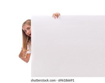 Surprised teen girl is popping out from the side of white blank banner and pointing at the board over white background