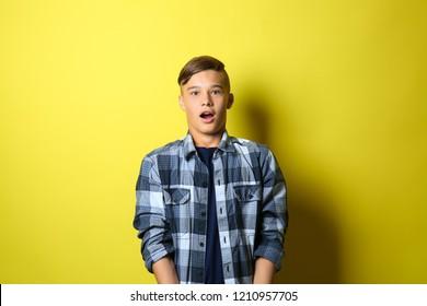 Surprised teenage boy on color background
