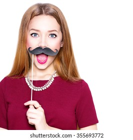 Surprised Teenage Girl holding funny mustache on stick. Joyful young woman ready for party, isolated on white background