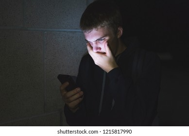 Surprised teenager covering his mouth after viewing something shocking on his phone. He is leaning against the brick wall of a high school at night.