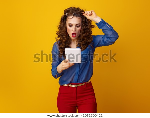 surprised trendy woman with long wavy brunette hair using tablet PC against yellow background