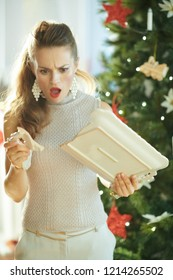 surprised trendy woman near Christmas tree looking at a broken dish