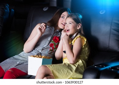 Surprised two smiling teen girls sitting at the cinema, watching a film and eating popcorn. movie theater.