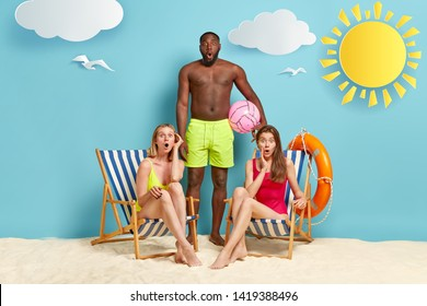 Surprised two women in bathingsuit, sit on deckchairs, dark skinned man stands near, wears green shorts, holds beach ball, stare together at camera with shock, find out about tragedy at sea.