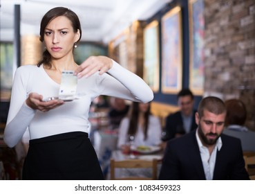 Surprised waitress woman holding a tray with money in a restaurant