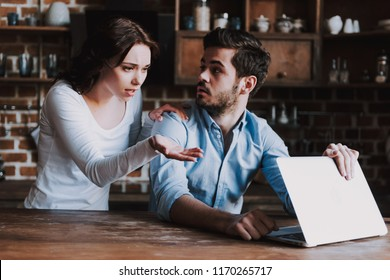 Surprised Wife Spying on Husband with Laptop. Wife Caught Husband Watching Pornographic Videos on Laptop or Texting with Mistress. Family Quarrel. Concept of Family Conflict.