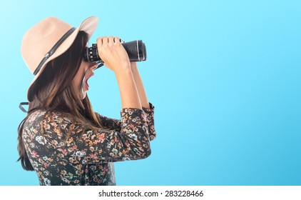 Surprised woman with binoculars over colorful background
