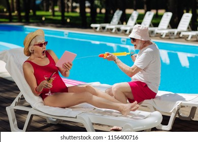 Surprised woman. Blonde-haired mature woman wearing bright red swimming suit feeling surprised with funny man