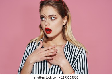 Surprised woman with bright make-up and in a striped shirt