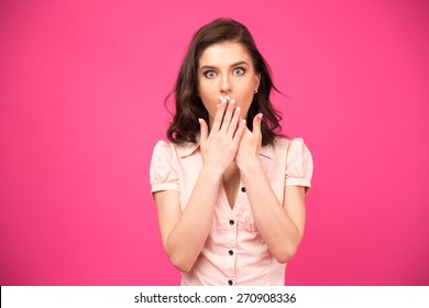 Surprised woman covering her mouth with hands over pink background and looking at camera