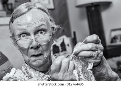 Surprised woman crocheting while looking at camera