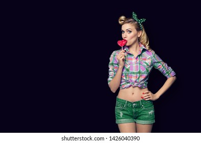 Surprised woman eating heart shape lollipop. Girl in pin up cloth. Blond model at retro fashion and vintage concept. Black color background. Copy space for some advertise slogan or text.