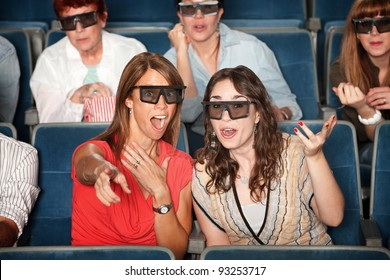 Surprised woman with friend in 3D glasses points index finger