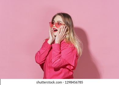 surprised woman with glasses holds hands on face on pink background