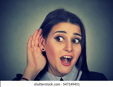 Surprised woman with hand to ear carefully secretly listening to gossip conversation isolated on gray background