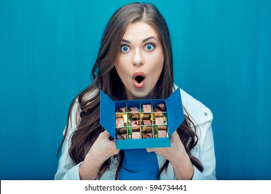 Surprised woman holding blue box with chocolate  candy. Blue wall background.