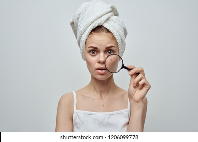 surprised woman holding a magnifier near pimples