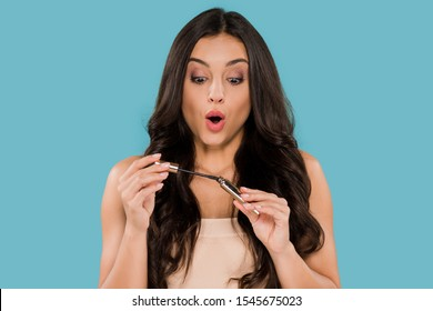 surprised woman holding mascara isolated on blue