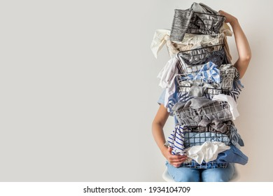 Surprised woman holding metal laundry basket with messy clothes on white background. Laundry. Isolated housewife. Copy space. Textile. Dirty wardrobe. Decluttering concept. Disorganized wife.