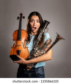 surprised woman holding musical instruments on a gray background