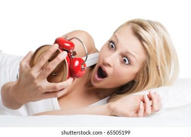 Surprised woman looking at alarm clock .