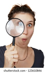 surprised woman looking through magnifying glass on white background