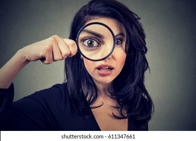 Surprised woman looking through magnifying glass isolated on gray wall background.