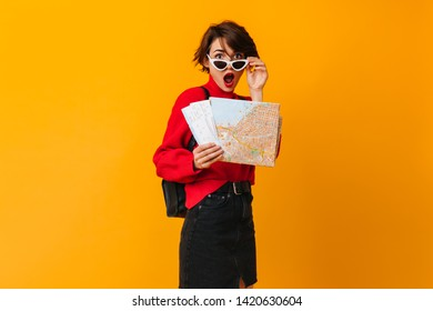 Surprised woman with map touching sunglasses. Studio shot of female tourist in red sweater.