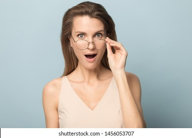 Surprised woman with open mouth in disbelief taking off glasses, hearing unexpected good news, astonished amazed female with wide open eyes looking at camera, isolated on studio background