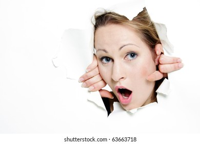 surprised woman peeping through hole in paper