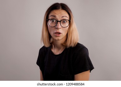 Surprised woman portrait in big glasses and black shirt. A girl with astonished face and open mouth on gray background
