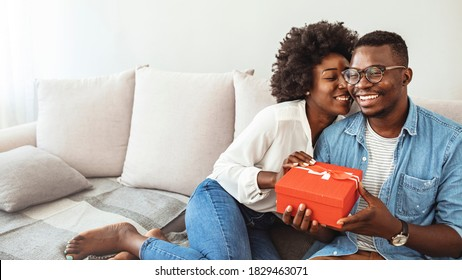 Surprised woman receiving Birthday present from her boyfriend. Young happy woman being surprised by her boyfriend with a birthday preset. Happy couple with gift box hugging at home.