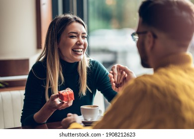 Surprised woman receiving gift box from boyfriend in a cafe