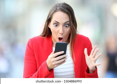 Femme surprise en rouge vérifiant le contenu du smartphone debout dans la rue