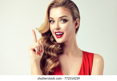 Surprised woman showing product .Beautiful girl with curly hair, pointing a finger at the top . Presenting your product. Expressive facial expressions . Teaching and edification .
