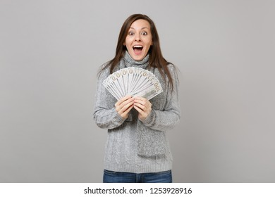 Surprised woman in sweater, scarf keeping mouth wide open, hold lots bunch of dollars banknotes, cash money isolated on grey background. Healthy fashion lifestyle people emotions, cold season concept