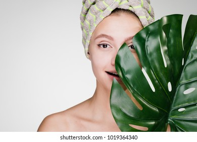 A surprised woman with a towel on her head holds a large green leaf.