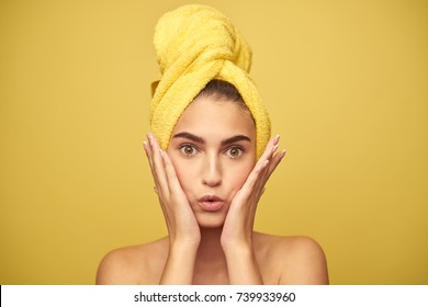 surprised woman with a towel on her head holding hands on her face on a yellow background, beauty, spa, clean skin