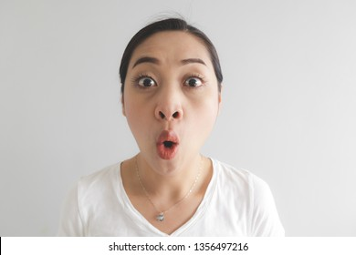 Surprised and wow face expression of Asian woman in white t-shirt. Concept of happy and impressive.