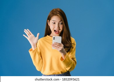 Surprised young Asia lady using mobile phone with positive expression, smiles broadly, dressed in casual clothing and standing isolated on blue background. Happy adorable glad woman rejoices success.