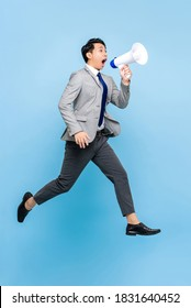 Surprised young Asian businessman jumping and shouting on megaphone isolated on light blue background