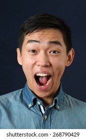 Surprised young Asian man crying and looking at camera