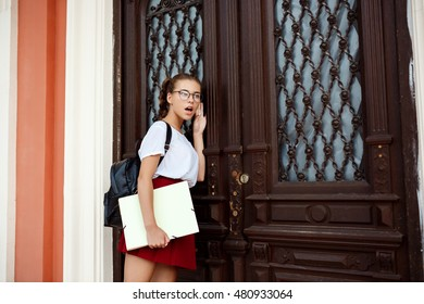 Surprised young beautiful female student in glasses standing near door, eavesdroping.